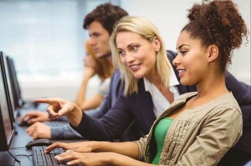 Profesor de mercadotecnia que apunta a la pantalla de la computadora de un alumno durante una lección sobre el texto alternativo